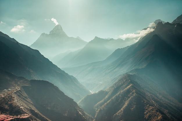 Der atemberaubende panoramablick auf den mächtigen nebligen schneebedeckten himalaya und die canyons mit den nadelwäldern. nepal. idealer hintergrund für die unterschiedlichsten collagen und illustrationen.
