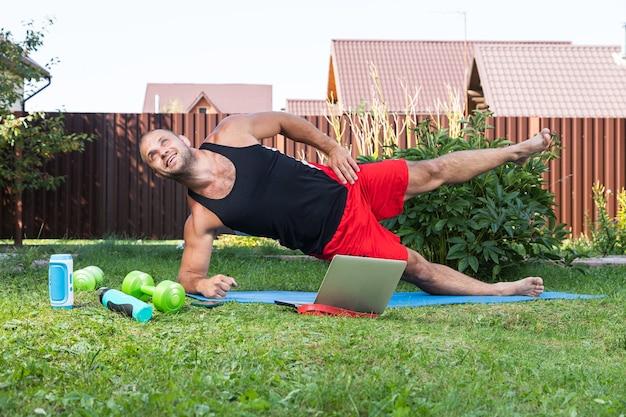 Der athlet hält die planke an der seite im hinterhof am sommertag gibt es ein offenes laptop-telefon