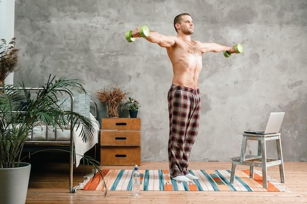 Der athlet im heimpyjama macht morgenübungen mit kurzhanteln