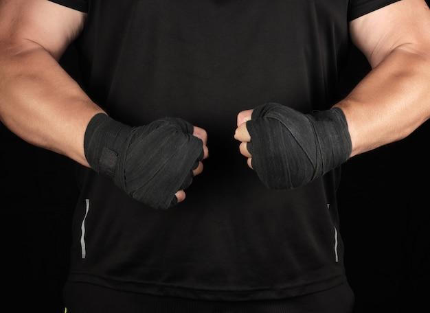 Der athlet in schwarzer uniform steht in einem gestell mit angespannten muskeln, seine hände sind in einen schwarzen textilverband gewickelt
