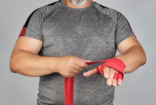 Der athlet steht in grauer kleidung und umwickelt seine hände mit roter textilbinde