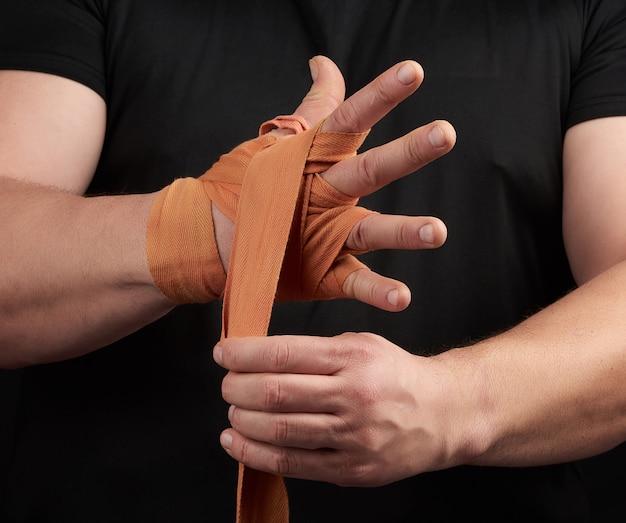 Der athlet steht in schwarzer kleidung und wickelt seine hände in einen roten elastischen orangefarbenen textilverband