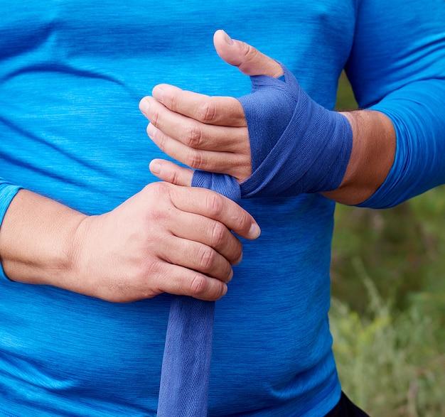 Der athlet steht und umwickelt seine hände mit einem blauen textilverband