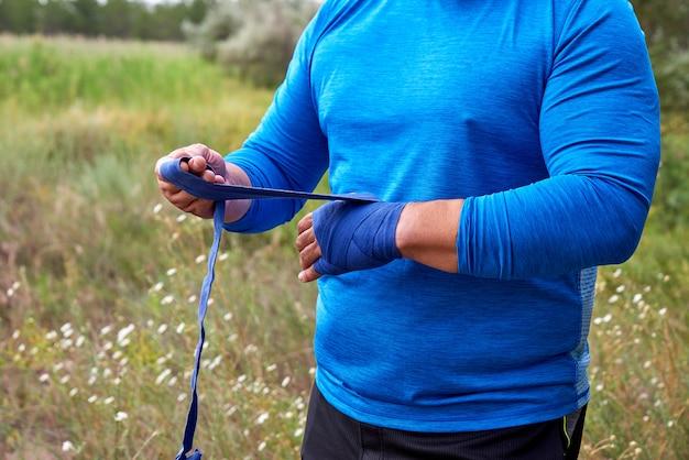 Der athlet steht und umwickelt seine hände vor dem training mit einem blauen elastischen textilverband