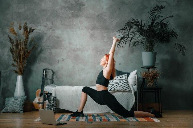 Der athlet streckte sich, meditierte und saß auf einem boden im schlafzimmer
