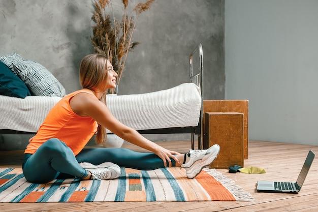 Der athlet streckte sich, meditierte und saß auf einer schnur im schlafzimmer