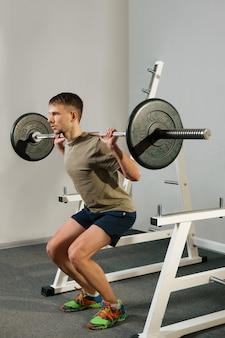 Der athletische mann, der hocken tut, trainieren mit dummkopf. starker mann macht langhantel kniebeugen.