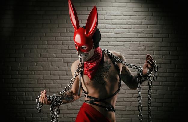 Der athletische mann in ketten als symbol für sklaverei und soziale gerechtigkeit angekettet in einer kaninchenmaske in roten farben