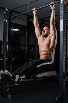 Der athletische mann trainiert die muskeln des unterleibs und hängt an der stange in der turnhalle