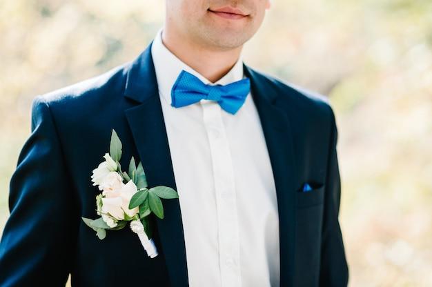 Der attraktive bräutigam mit fliege in anzug mit boutonniere oder knopfloch auf jacke steht auf dem hintergrundgrün im garten, park. natur. beschnittenes foto.