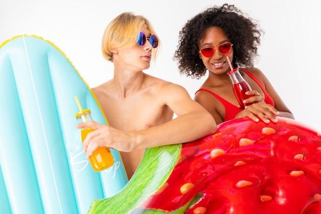 Der attraktive europäische mann und das afrikanische mädchen in badeanzügen trinken cocktails und halten einen schwimmkreis