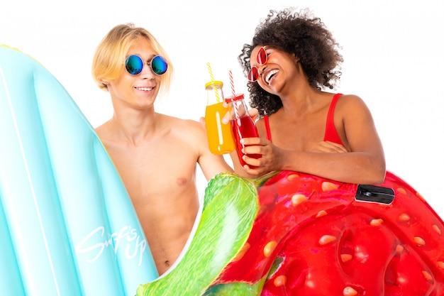 Der attraktive europäische mann und das afrikanische mädchen in badeanzügen trinken cocktails und halten schwimmmatratzen