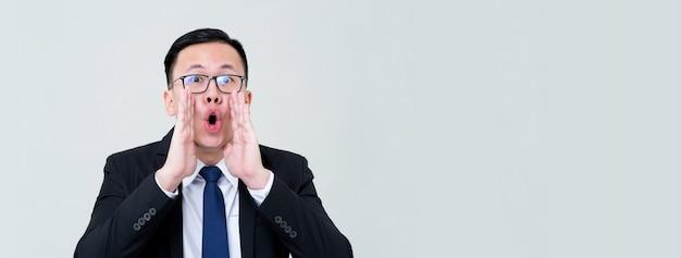 Der aufgeregte junge asiatische geschäftsmann, der mit den händen schreit, schalenförmig um den lokalisierten mund