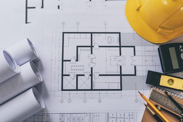 Der aufgerollte architektenhausplan plant auf dem tisch, hohe winkelsicht.