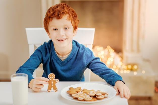 Der aufregendste tag. entzückender junge mit den lockigen haaren, der an einem tisch sitzt und fröhlich lächelt, während er sein köstliches frühstück an einem weihnachtsmorgen genießt.