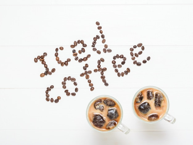 Der aufschrifteiskaffee und zwei gläser kaffee mit stücken eis auf einem weißen holztisch.