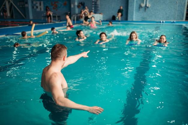 Der ausbilder arbeitet mit dem unterricht im schwimmbad