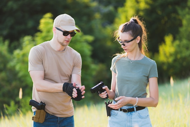 Der ausbilder bringt dem mädchen bei, eine pistole auf die strecke zu schießen
