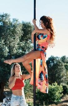 Der ausbilder hilft dem jungen pole-tänzer in einem kleid, auf einer tragbaren plattform gegen den garten eine pose einzunehmen
