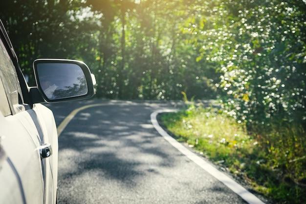 Der außenspiegel eines autos mit naturstraße.