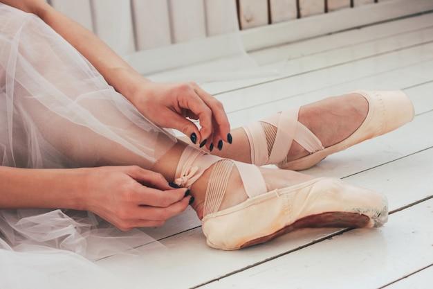 Der authentische ballerina-balletttänzer, der auf dem boden sitzt und spitzenschuhe bindet, abschluss oben