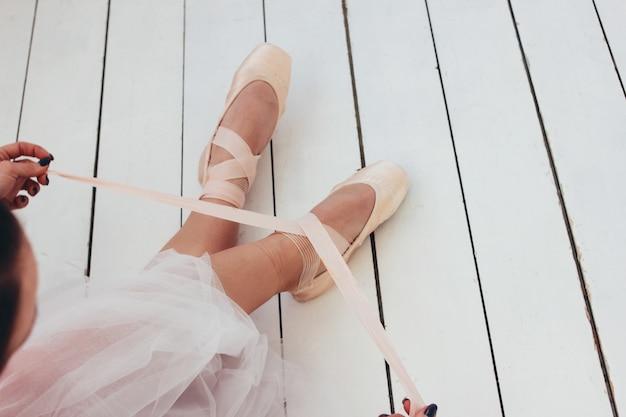 Der authentische ballerina-balletttänzer, der auf dem boden sitzt und spitzenschuhe bindet
