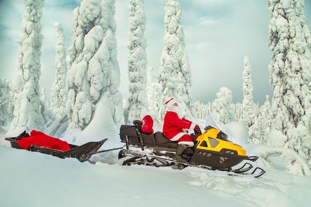 Der authentische weihnachtsmann fährt mit dem schneemobil durch den winterwald.