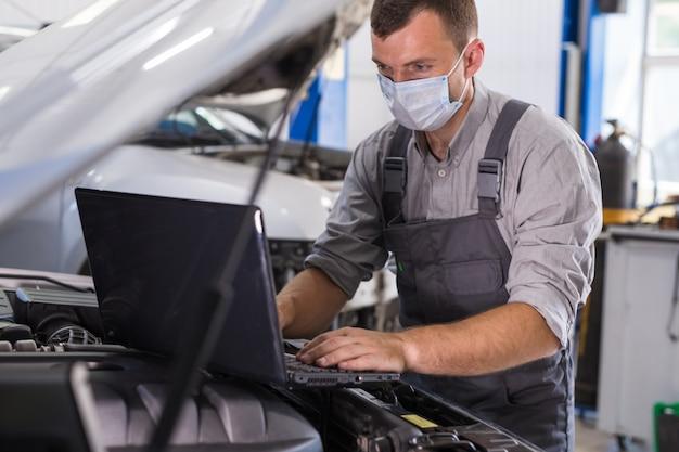 Der auto-servicemitarbeiter führt diagnosen und autoreparaturen im raum durch.