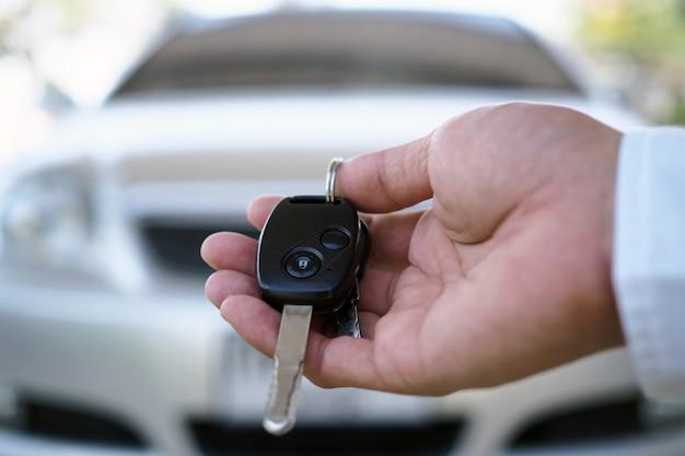 Der autobesitzer hält dem käufer die autoschlüssel bereit.