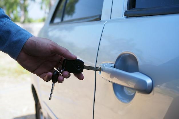 Der autobesitzer öffnet mit dem schlüssel die autotür.