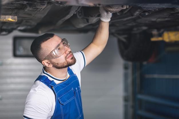 Der automechaniker eines jungen mannes in overalls an seinem arbeitsplatz repariert die federung des autos