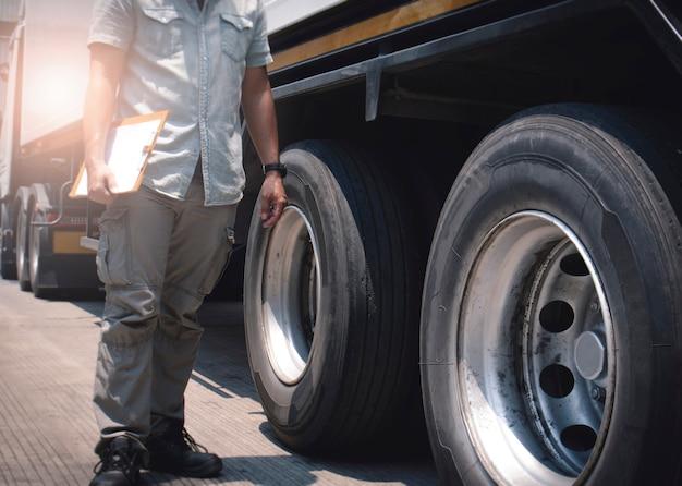Der automechaniker-fahrer, der die zwischenablage hält, überprüft die sicherheit der lkw-räder und -reifen