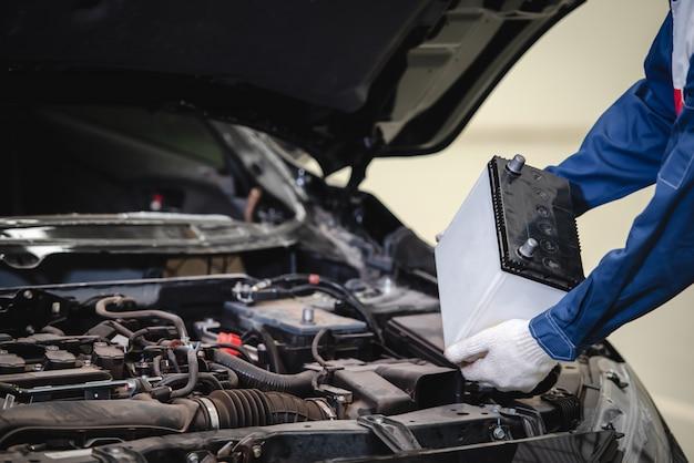 Der automechaniker ist dabei, eine neue batterie für die kunden auszutauschen, die den batteriewechselservice im geschäft nutzen.
