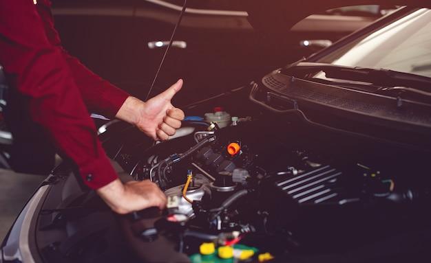 Der automechaniker prüft die verfügbarkeit eines guten und sicheren fahrbegleiters.