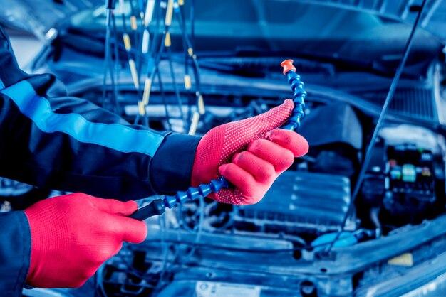 Der automechaniker überprüft den spannungspegel mit einem voltmeter.