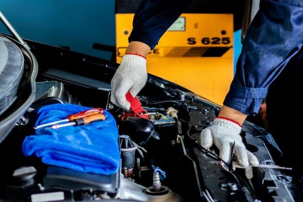 Der automechaniker überprüft die batteriekapazität des fahrzeugs.