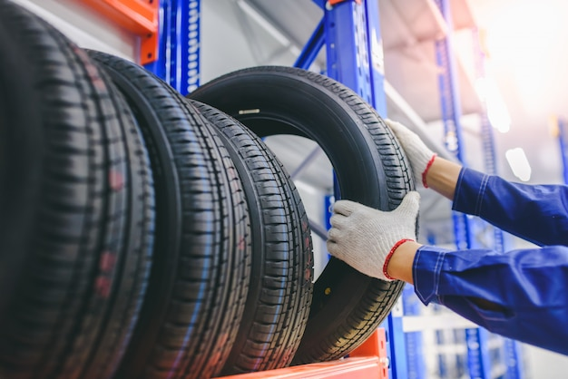 Der automechaniker wechselt neue reifen auf lager, um sie für kunden in der garage zu wechseln - räder / reifen wechseln.
