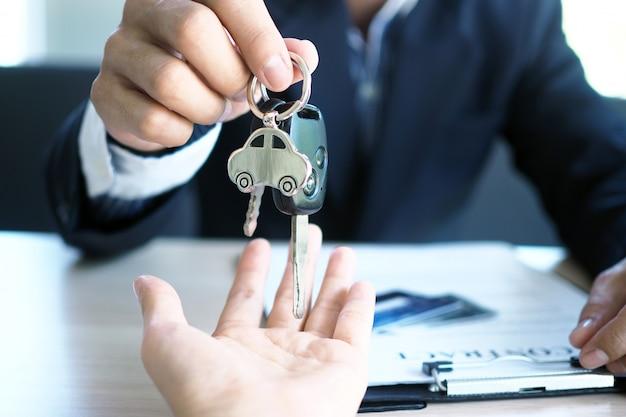 Der autoverkäufer und der schlüssel zum neuen besitzer.