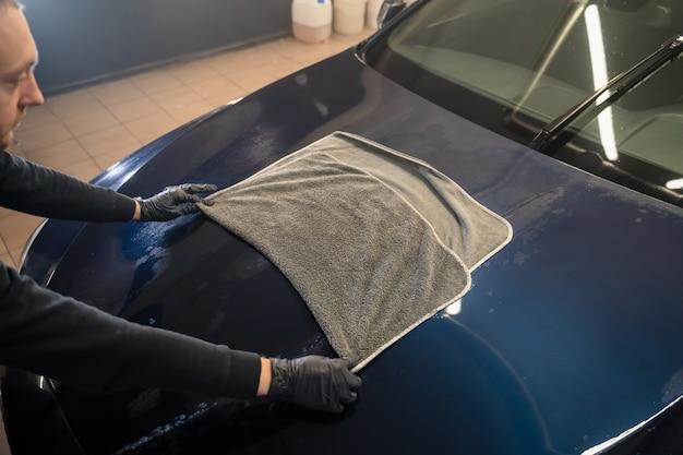 Der autowascharbeiter wischt das auto nach dem waschen mit einem mikrofasertuch ab.