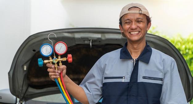 Der autowerkstattmann überprüft den motor und das kühlsystem, bevor er in einen langen urlaub fährt. konzept der autopflege und -wartung von experten