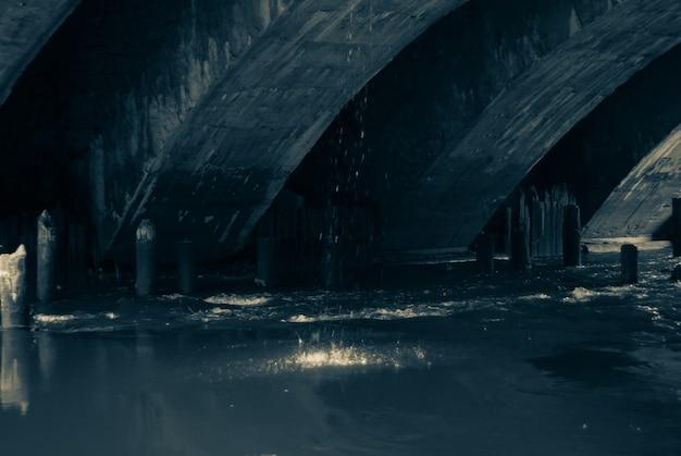 Der bach fließt unter der alten brücke mit bogengewölben und den resten von holzpfählen