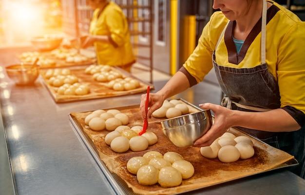 Der bäcker schmiert die brötchen zum weiteren backen mit sonnenblumenöl ein.