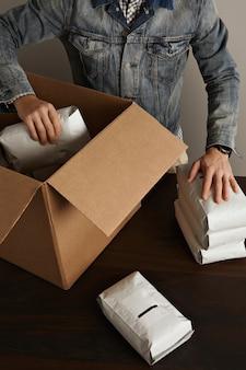 Der bärtige brutale mann in der jeans-arbeitsjacke legt leere versiegelte hermetische pakete in eine große karton-papierbox auf einen holztisch. sonderlieferung