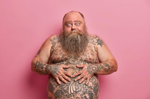 Der bärtige dicke kerl hält die hände auf dem großen, tätowierten bauch, hat die augen abgehört, hat den dicken bart und posiert an der rosa wand. nackter übergewichtiger erwachsener mann mit großem bauch, fragt rat, wie man gewicht verliert