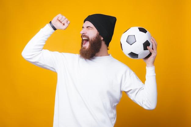 Der bärtige freudige mann schreit und feiert und hält einen fußball an der gelben wand.