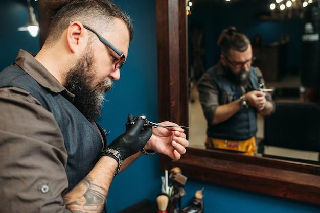 Der bärtige friseur bereitet instrumente und arbeitsplatz für den haarschnitt vor