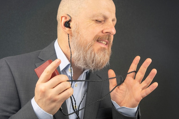 Der bärtige geschäftsmann hört gerne seine lieblingsmusik über einen audioplayer in kleinen kopfhörern.