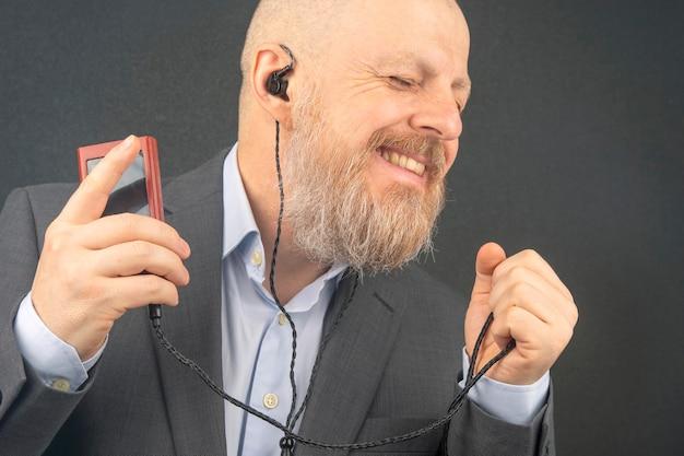 Der bärtige geschäftsmann hört zu hause gern seine lieblingsmusik mit einem audioplayer in kleinen kopfhörern. audiophiler und musikliebhaber. musik und hifi-sound.