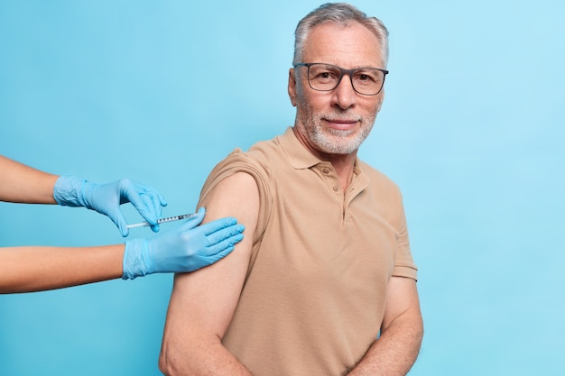 Der bärtige grauhaarige senior erhält eine impfung gegen coronavirus, schützt sich vor viren, trägt eine brille und ein t-shirt sieht bestimmt isoliert über der blauen wand aus