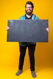 Der bärtige hipster der kamera lächelt und hält eine saubere tafel in der hand